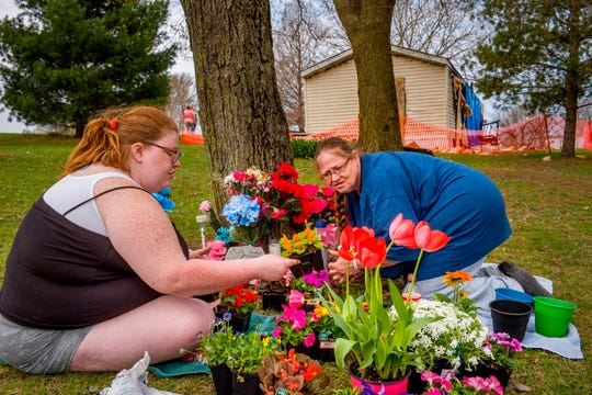 Katie Alwood, left, and her mother, Lori Alwood, plant flowers April 17, 2019 near the Goodfield mobile home, in background, where five relatives died in an April 6 fire.