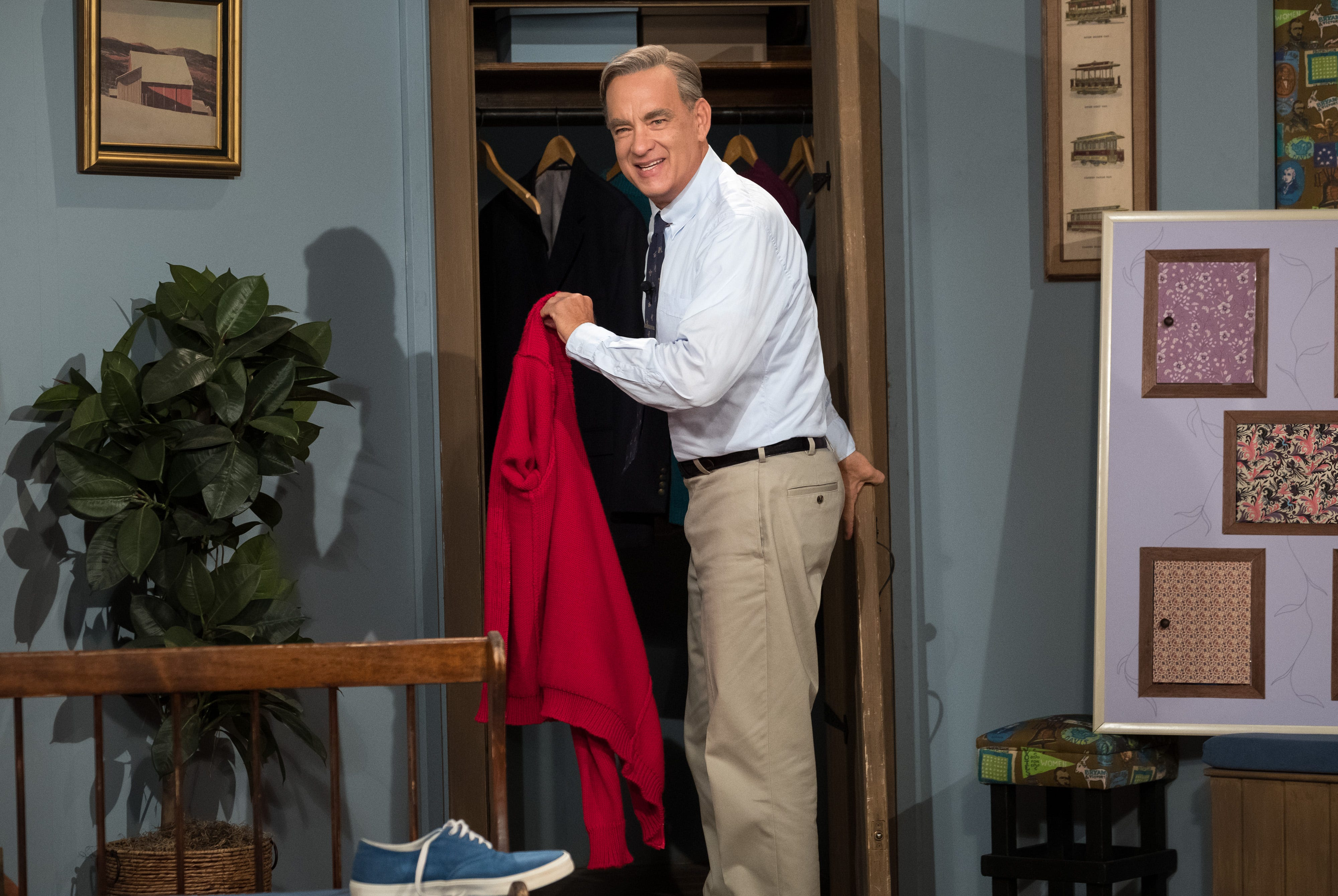 "Tom Hanks wears the red sweater and wise demeanor of children's TV icon Mister Rogers in ""A Beautiful Day in the Neighborhood."""