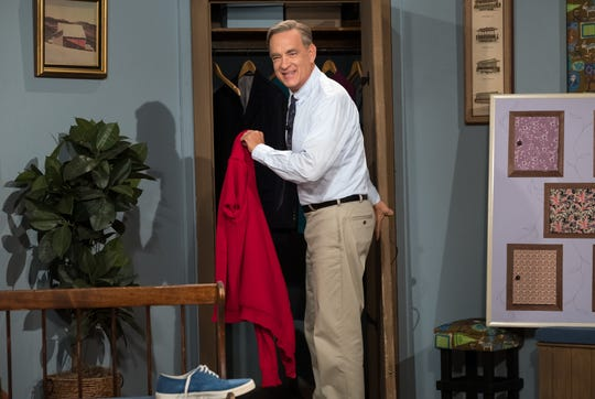 """Tom Hanks wears the red sweater and wise demeanor of children's TV icon Mister Rogers in """"A Beautiful Day in the Neighborhood."""""""