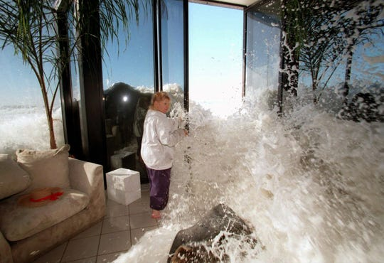 Marilyn Lane attempts to close her doors to prevent a large wave from crashing into the living room of her home near Ventura, Calif., in this Jan. 30, 1998, file photo.  In 1997-98, several storms fueled by a strong El Nino slammed into California, killing 17 and causing an estimated $550 million in damaged crops and property.