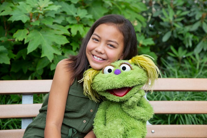 "Salia Woodbury, whose parents are in recovery, with ""Sesame Street"" character Karli."