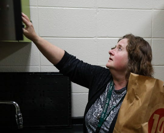 Stacie Christian looks through the cabinets of UW-Green Bay's Campus Cupboard in Rose Hall on Monday, Oct. 21, 2019.