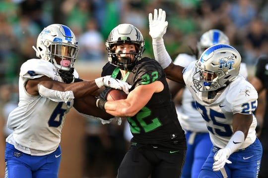 North Texas wide receiver Michael Lawrence (32) carries the ball after a catch, while being defended by Middle Tennessee linebacker Khalil Brooks (6) and defensive back Desmond Anderson (25) during the second half Saturday, Oct. 19, 2019, in Denton.