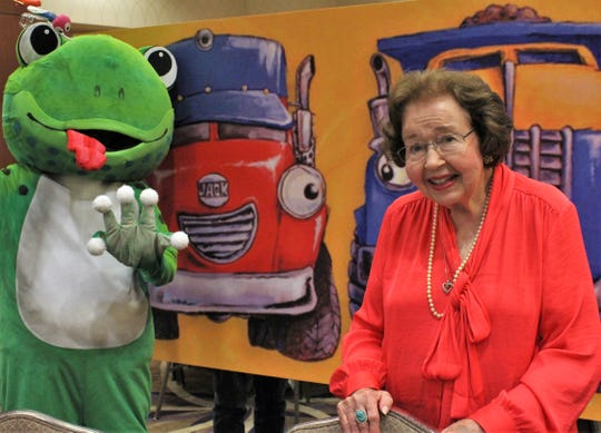 """Longtime arts and Abilene Zoo supporter Gail Russey poses for a photo in front a Loren Long prop only to have Frog (no other name provided) """"photo bomb"""" Wednesday after the Celebrate the Arts in Abilene luncheon at Abilene Christian University."""