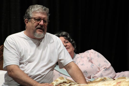 """Linda Loman (Pam Peraza) sings soothingly to her husband Willy (Gary Varner) in bed in this rehearsal scene from """"Death of a Salesman."""""""