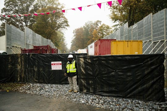 In this Tuesday, Oct. 22, 2019 photo, a worker stands by the gate of a construction site along the Mariner East pipeline in Exton, Pa. The 350-mile (560-kilometer) pipeline route traverses those suburbs, close to schools, ballfields and senior care facilities. The spread of drilling, compressor stations and pipelines has changed neighborhoods — and opinions.  (AP Photo/Matt Rourke)