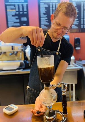 Luke Ragsdale uses a siphon to make tea at Bold Cup Coffee in Viera.