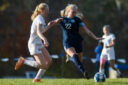 MMU's Willa Clark (22) kicks the ball down the field past South Burlington's Madison King-Thurber (19) during the first round of the high school girls playoff game between the South Burlington Wolves and the Mount Mansfield Cougars at MMU High School on Wednesday afternoon October 23, 2019 in Jericho, Vermont.