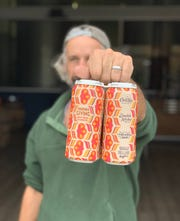Double Nickel head brewer and co-founder Drew Perry hoists a four-pack of Friends Giving 'Potluck-Style' Hazy IPA. Proceeds from the beer will feed te hungry.