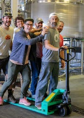 Friends and brewers give Double Nickel co-founder and head brewer Drew Perry a ride on the loading dock during a Friends Giving brewing day. From left are Eli Facchinei of Tonewood Brewing Co.; Chris Henke, of Cape May Brewing Co.; John Dalsey and Brian Needham of Double Nickel, and Dave Goldman of Urban Village.