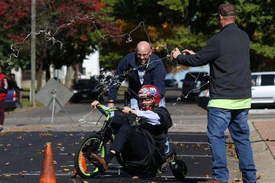 Coshocton County Common Pleas Judge Bob Batchelor gets sprayed by silly string as he makes his way down Fourth Street on a tricycle during a race to raise money for the United Way of Coshocton County on Wednesday.