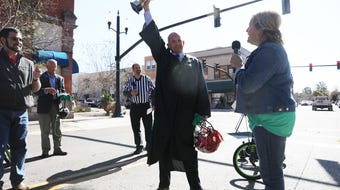 Commissioners Clerk Mary Beck explains rules for the final race of a United Way fundraiser Wednesday on the court square with elected officials racing on tricycles.