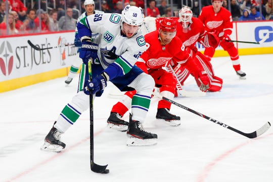 Vancouver Canucks center Tim Schaller (59) skates with the puck chased by Detroit Red Wings defenseman Trevor Daley (83) in the first period at Little Caesars Arena on Tuesday, Oct. 22, 2019, in Detroit.