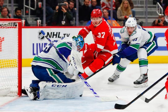 Vancouver Canucks goaltender Jacob Markstrom (25) makes a save on Detroit Red Wings left wing Evgeny Svechnikov (37) defended by defenseman Oscar Fantenberg (5) in the second period at Little Caesars Arena on Tuesday, Oct. 22, 2019, in Detroit.