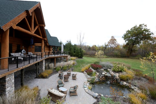 Five acres of grounds surround the log house, although it's in a gated subdivision. A side-to-side deck wraps around, and its deep center peak provides rain shelter. Current owners added the double pond, waterfall and stone garden.