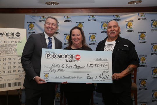 Michigan Lottery Commissioner Brian O. Neill, left, presents Powerball jackpot winners, Phillip and Dawn Chippewa, with a check for $80 million.