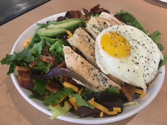 """The """"BAE""""  salad with applewood smoked bacon, avocado, dippy egg, sharp cheddar, topped with grilled chicken over field greens."""