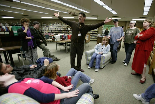 Ken Bignotti, center, a teen services librarian at Livonia's Alfred Noble Library at 32901 Plymouth Road in Livonia shows members of the Livonia Teen Advisory Committee where they can hang a mobile in the teen area of the library in this Wednesday, February 25, 2004 photo.