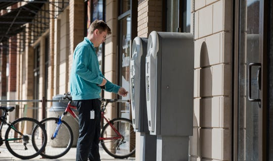 Garret Gotaas of Clarkston pays for parking at a meter station outside Emagine Royal Oak in Royal Oak, Mich. on Monday, Oct. 21, 2019.