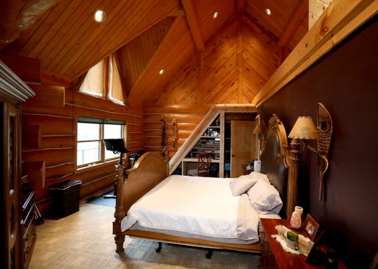 The ceiling in the owners' suite shows interior wood mitered into many gables. The current owners added a  loft above the bed, with slanting ladder steps, room for a massage table and a cedar closet. They suite's showy 17-foot owners' bath has a door out to the deck and hot tub.   The home is in Genoa Township on Tuesday, Oct. 22, 2019.