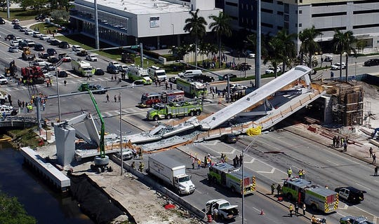 FILE - In this March 15, 2018, file photo, emergency personnel respond after a new pedestrian bridge collapsed onto a highway at Florida International University in Miami.