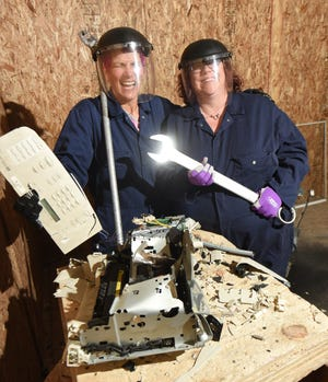 Samantha Banda, left, of Chelsea and Rose Snowwhite of Dexter show off their smashed fax machine at the Destruction Depot, a rage room in Whitmore Lake.