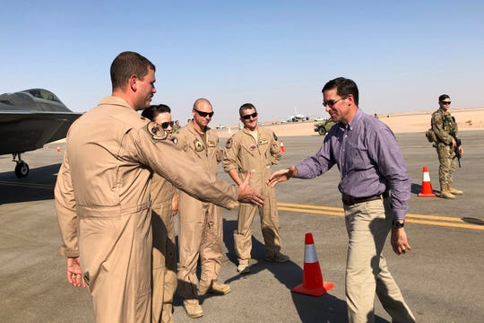 Defense Secretary Mark Esper talks with U.S. troops in front of an F-22 fighter jet deployed to Prince  Sultan Air Base in Saudi Arabia, Tuesday, Oct. 22, 2019.