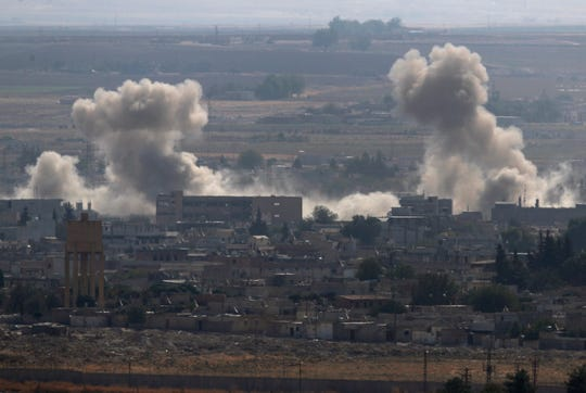 In this photo taken from the Turkish side of the border between Turkey and Syria, in Ceylanpinar, Sanliurfa province, southeastern Turkey, smoke and dust billows from targets in Ras al-Ayn, Syria, caused by bombardment by Turkish forces, Tuesday, Oct. 15, 2019.