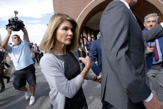FILE - In this Aug. 27, 2019 file photo, actress Lori Loughlin departs federal court in Boston after a hearing in a nationwide college admissions bribery scandal.  Loughlin, her fashion designer husband, Mossimo Giannulli, and nine other parents face new charges in the college admissions scandal.