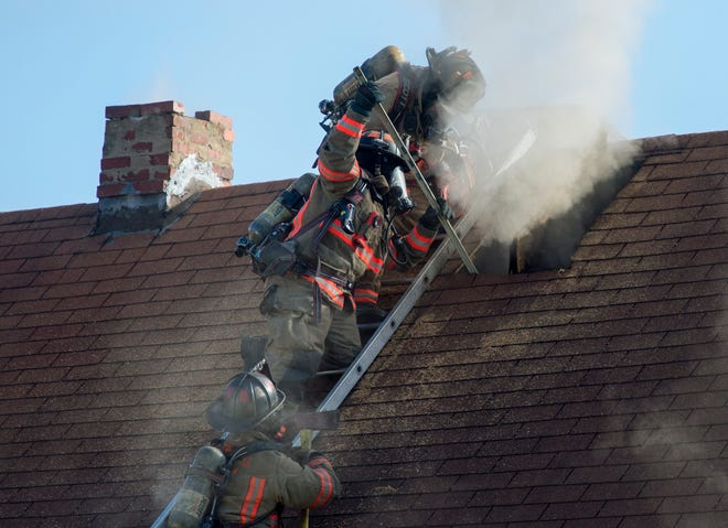Evansville Firefighters cut a hole in the roof of 412 E. Franklin St. while attempting to extinguish a fire Wednesday morning, Oct. 23, 2019.