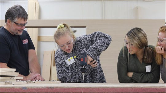 Al Sommers of CTI Hospitality looks on with Luxemburg-Casco High School freshmen Mariah McFeely and Savanna Rowell, right, as L-C freshman Madelynn VanIten tries a power drill during Kewaunee County Manufacturing Career Day on Oct. 15.