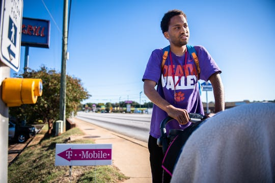 """Azaivn Burnside of Greenville pauses during a 40-minute walk down White Horse Road with his 2-year-old nephew on Wednesday afternoon, Oct. 23, 2019, to visit a friend. """"I'm going to see my home boy,"""" he said."""