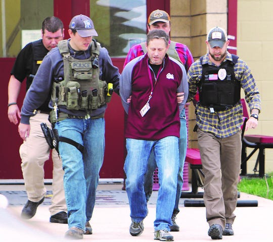 Anthony Heaton being escorted by law enforcement. Heaton was arrested on Friday, Sept. 27 during an investigation into his alleged relationship with a former student.