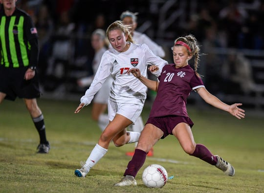 Henderson County's Morgan Green (20) makes a pass under defensive pressure from Daviess County's Sophie Jagoe (17) as the Henderson County Lady Colonels play the Daviess County Lady Panthers in the first round of the state tournament at Henderson's Colonel Field Tuesday evening, October 22, 2019.