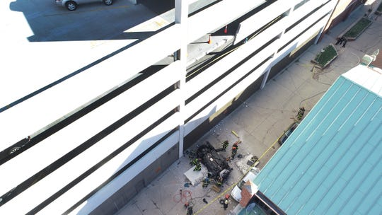 A vehicle is seen on East Wabash Street near City Market. A section of concrete wall is missing from the third floor of a parking garage.