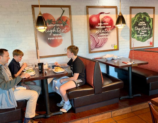 Matt DeVoss of Madison, left, eats dinner with his sons, Karcher DeVoss and Meritt DeVoss, in the newly renovated Newk's on Lake Harbour Drive. The inspirational artwork on the wall is new.