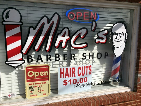 The sign on the window of Mac's Barber Shop has the likeness of Doug McNelly's dad.