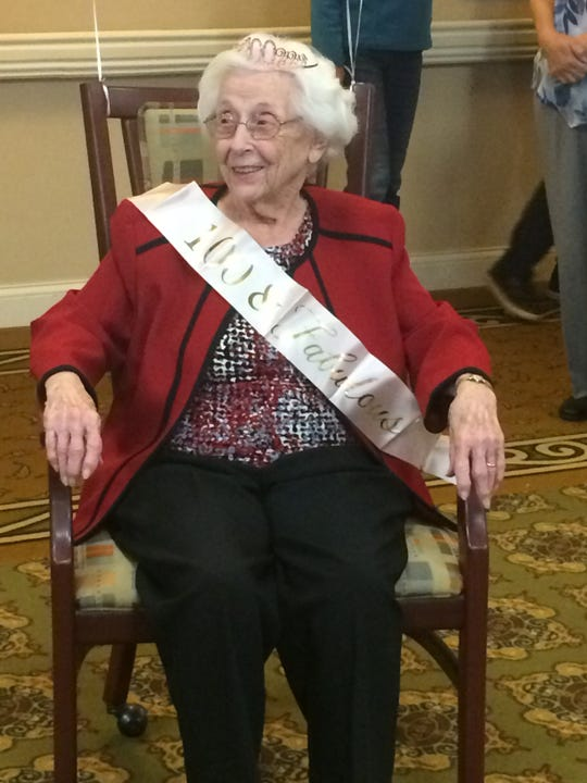 "Thelma Davis proudly wears the sash: ""100 and Fabulous"" at her birthday party."