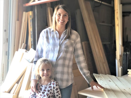 "The creator of Izzy's Attic custom made furniture and décor, Meagan Kahn, with her daughter Isabella in her Halls workshop on Oct. 22. ""My husband and I always knew we wanted one of us to stay home and raise our daughter,"" said Kahn. ""I was refinishing furniture as a hobby. I decided to take it a step further. I wanted to help out, too."""