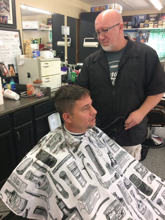 Jeff Martin, who owns Security Equipment Co. near Mac's Barber Shop, stops in on a break for a haircut from Doug McNelly. 2019
