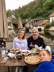 Kurt Stimens and his wife Oxana enjoy dinner in Brantome, France, with Oxana's son Gabriel.