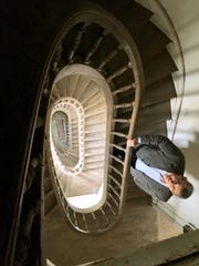 Kurt Stimens' realtor Daniel Arnold stands inside the castle's winding staircase.