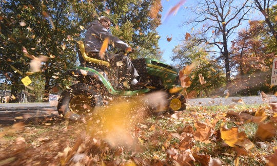 Ted Sazdanoff uses his mower to blow leaves Wednesday afternoon in the Woodland neighborhood.