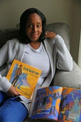 "Ebony Lewis holds the book she authored, ""Dear Black Boy: It's Ok To Cry."""