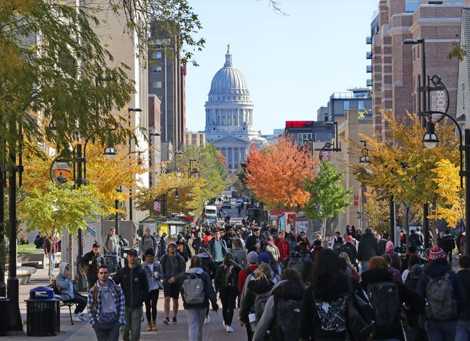 Students walk to classes on campus along State Street with the State Capitol in the background at the University of Wisconsin-Madison on Oct. 23, 2019.
