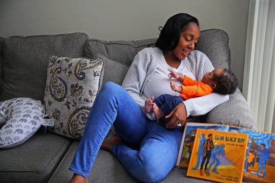 Ebony Lewis holds her baby, Daxson, who was born a month after her book published.
