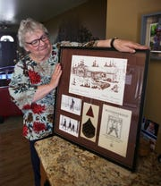 Mary Schueller shows a framed photo board at her home in Hartford containing photos of her father, Mike Kerkes, and memorabilia from his time serving in the CCC, including two of his patches and an architectural drawing of the combination building he helped build at Copper Falls State Park in Mellen from 1935 to 1937.