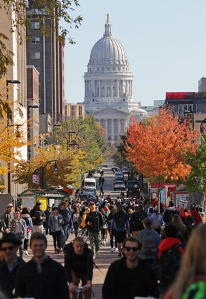 Students walk to classes on campus along State Street with the Madison state capitol in the background at the University of Wisconsin Madison on Wednesday, Oct. 23, 2019.