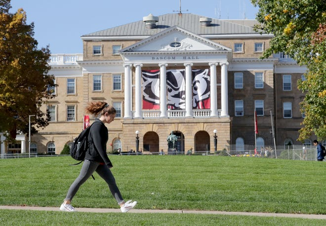 A student walks to classes on campus past Bascom Hall at the University of Wisconsin-Madison in October. The state's flagship just hit its lowest average time to graduation in history.
