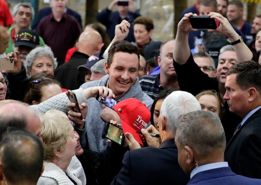 Erik Frafjord, a student at Sussex Hamilton High School, gets his Trump hat signed by Vice President Mike Pence  Wednesday at Uline Warehouse in Pleasant Prairie, Wisconsin.